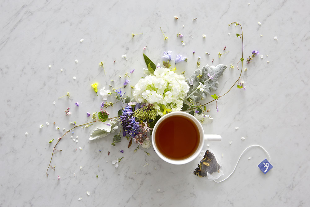 Aerial shot of cup of tea with floral decorations