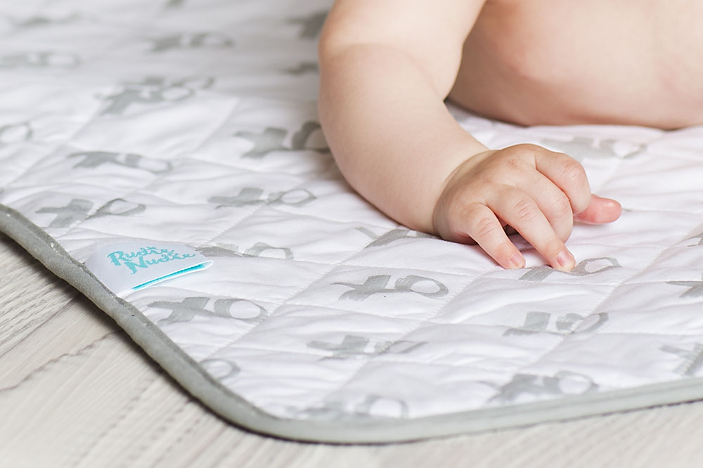cropped picture of baby on play mat
